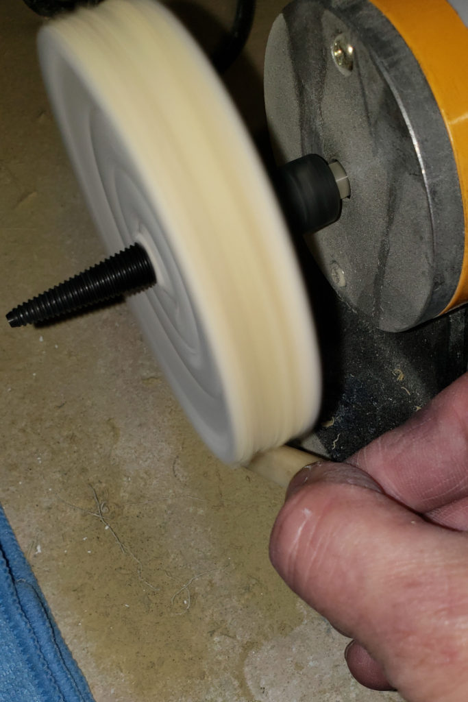 Polishing a guitar nut on buffing wheel